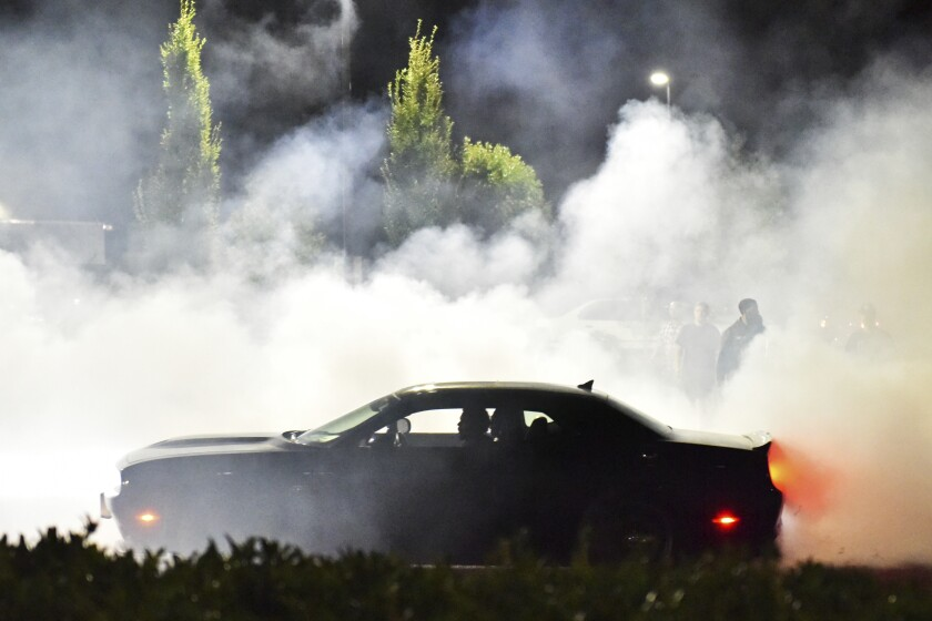 Street racers gather the evening of Sunday, Aug. 12, 2018, in the parking lot of the Goodwill on Northeast Marine Drive and 122nd Avenue in Portland, Ore. Across America, police are confronting illegal drag racing whose popularity has surged since the coronavirus pandemic and lockdowns began. Drivers have blocked off roads to race and to etch donut patterns on pavement with the tires of their souped-up cars. From Portland, Oregon; to Albuquerque, New Mexico; from Nashville, Tennessee; to New York City, officials are reporting a dangerous, and sometimes deadly, uptick in street racing.(Anna Spoerre /The Oregonian via AP)
