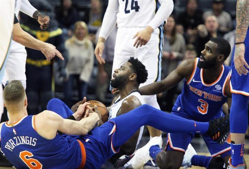 El jugador Tyreke Evans (c) de Memphis Grizzlies disputa un balón con Kristaps Porzingis (i) de New York Knicks hoy, miércoles 17 de enero de 2018, durante un juego entre New York Knicks y Memphis Grizzlies de la NBA, que se disputa en el FedEx Forum en Memphis, Tennessee, (Estados Unidos). EFE