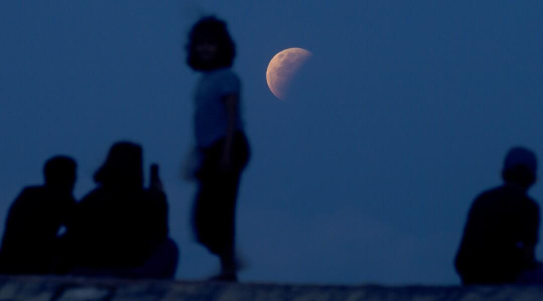 L'ombra della Terra attraversa la luna mentre i residenti guardano sulla spiaggia di Sanur