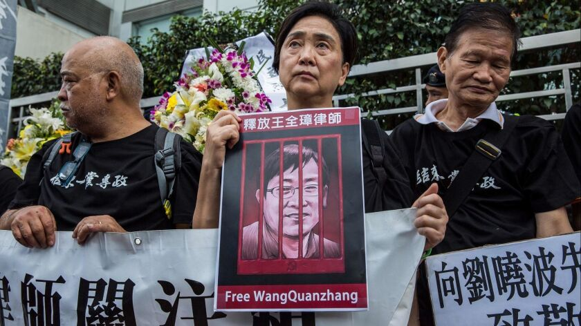 Former Hong Kong lawmaker Emily Lau, center, holds a picture of detained Chinese human rights lawyer Wang Quanzhang at a rally on April 5, 2018.