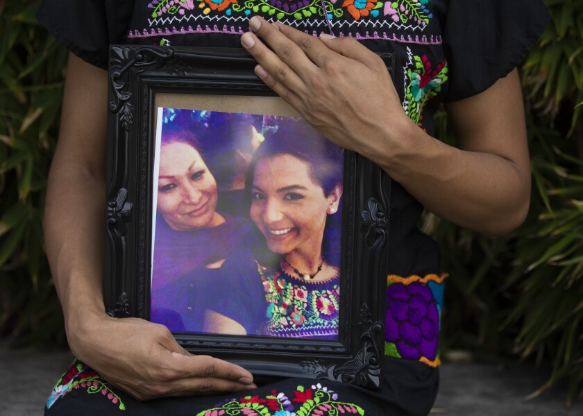 A portrait of Pink Moon Midnight Blue holding a photo of her friend Angela Martinez, left.