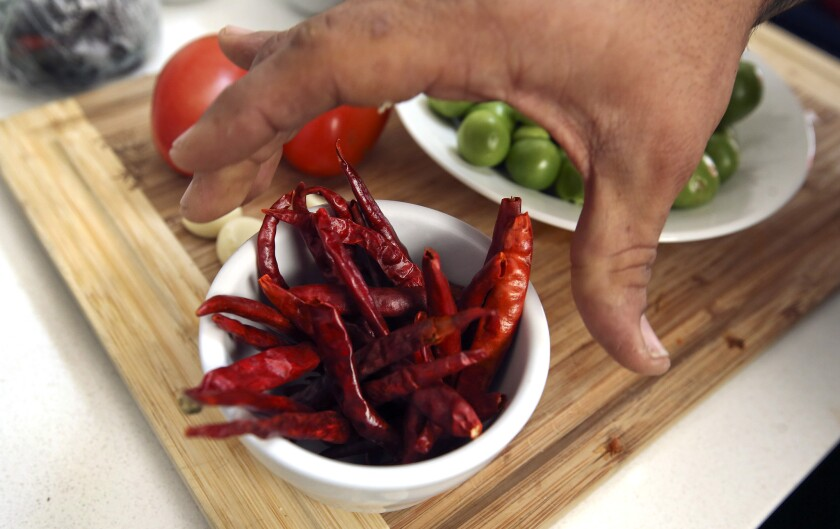 Wes Avila of Guerrilla Tacos grabs a cup of peppers, while preparing to make his sweet potato breakf