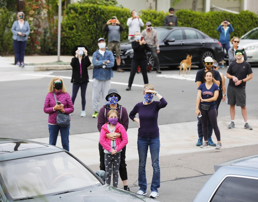 Fans watch as opera singer Victoria Robertson, a soprano, sings from the porch of her North Park home on April 19, 2020. Not everyone was wearing face masks.
