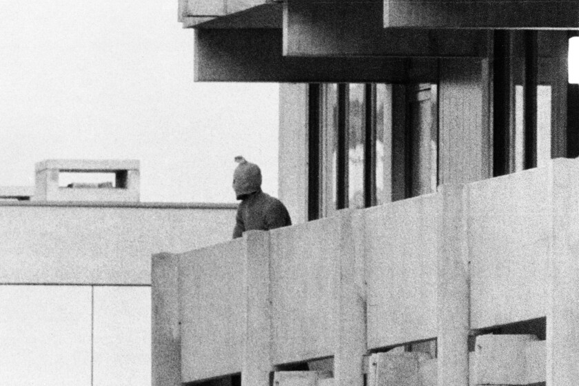 FILE - On Sept. 5, 1972, a Palestinian commando group seizes the Israeli Olympic team quarters at the Olympic Village in Munich, Germany. A member of the commando group is seen here as he appears with a hood over his face on the balcony of the building, where they hold several Israeli athletes hostage. (AP Photo/Kur Stumpf, File)