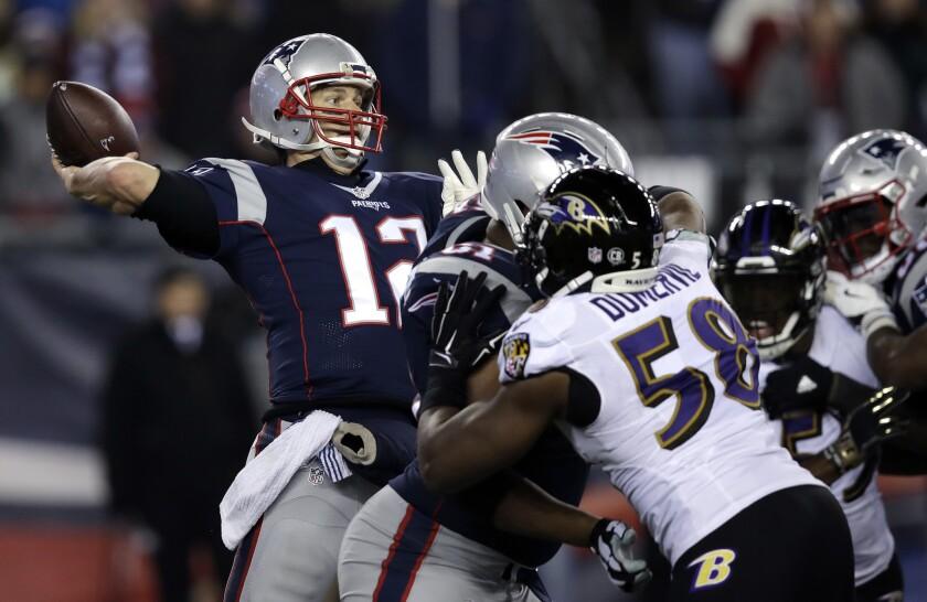 El quarterback de los Patriots de New England Tom Brady (12) lanza un pase de touchdown a Chris Hogan ante la presión del linebacker de los Ravens de Baltimore Elvis Dumervil (58) durante el último cuarto del juego de la NFL que enfrentó a ambos equipos, el 12 de diciembre de 2016, en Foxborough, Massachusetts. (AP Foto/Charles Krupa)