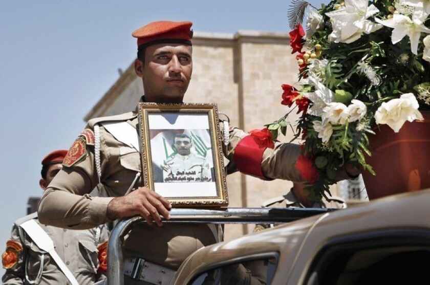 An Iraqi soldier holds a picture of a slain comrade during a Baghdad funeral procession for five soldiers killed by gunmen. Violence has racked the country for a week, prompting the government to shut down TV stations it said were encouraging sectarian conflict.