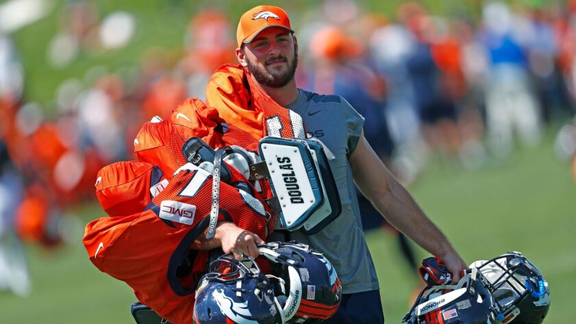 Denver Broncos tight end Jake Butt carries the helmets and pads of veteran players after drills at an NFL training camp in July.