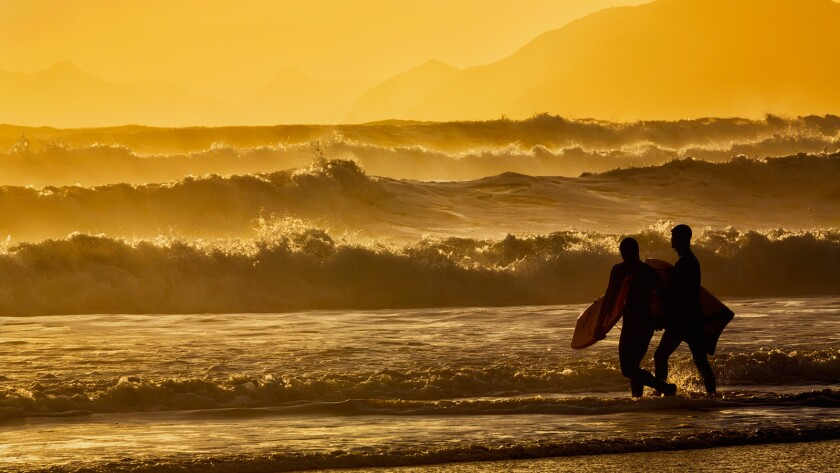 Body surfers walk in the water on the coast of Alaska's Kodiak Island during late afternoon in Pasagshak State Park.