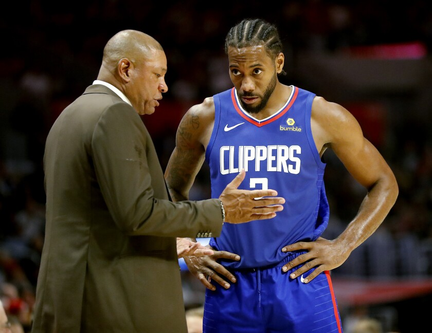 Clippers coach Doc Rivers talks with forward Kawhi Leonard during a game earlier this season.