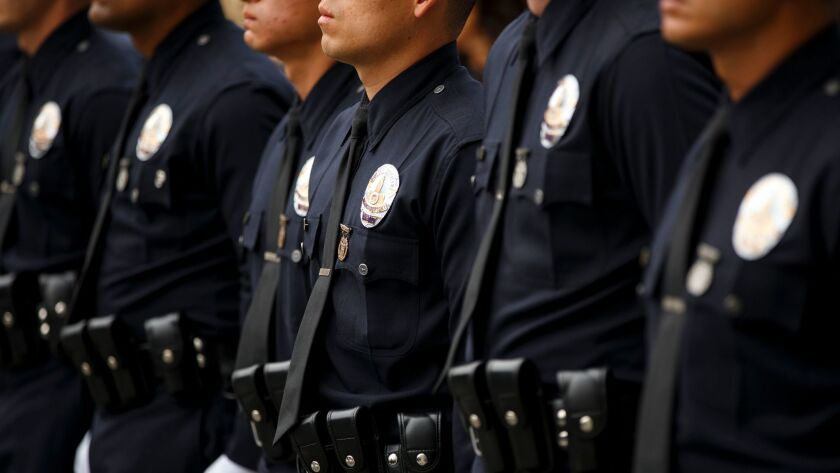New Los Angeles police officers stand at attention during a graduation ceremony last year.