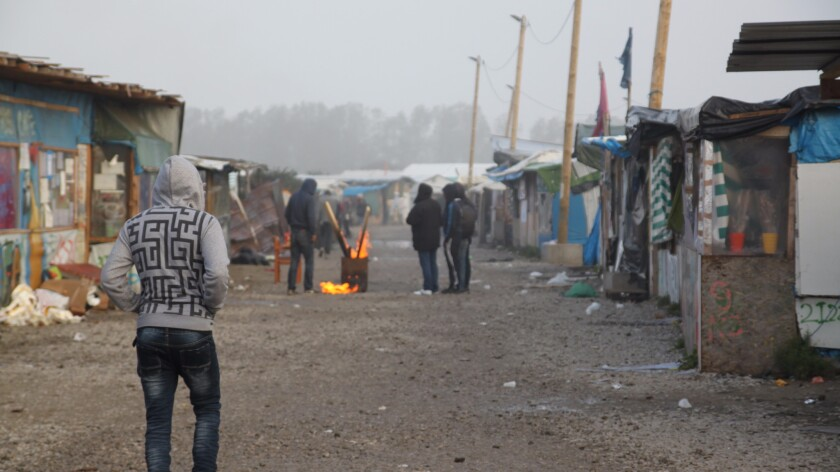 A young man walks through the camp early Sunday morning.