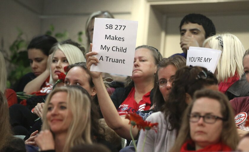 An audience member holds a sign expressing opposition to SB 277, which would end personal-belief exemptions from California's vaccination mandate for schoolchildren, as lawmakers discuss the bill at the Capitol last month.