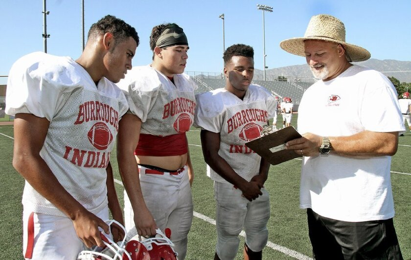 Burroughs head football coach Keith Knoop, right, is the All-Area Football Coach of the Year. Here he's talking to players (left to right) Cole Gurley, Anthony Garcia and Chance Bell during summer practice. (Photo by Ross A. Benson)