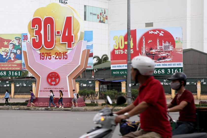 People ride past billboards marking the 40th anniversary of the end of the Vietnam War, in Hanoi, on Tuesday.