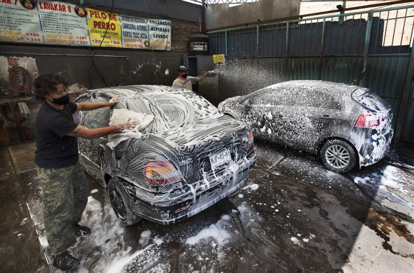 Óscar Aguilera y Juan Martínez lavan automóviles el viernes 31 de julio de 2020 en el autolavado Lavakar, en la Ciudad de México. Ambos portan mascarillas para protegerse del coronavirus. (AP Foto/Marco Ugarte)