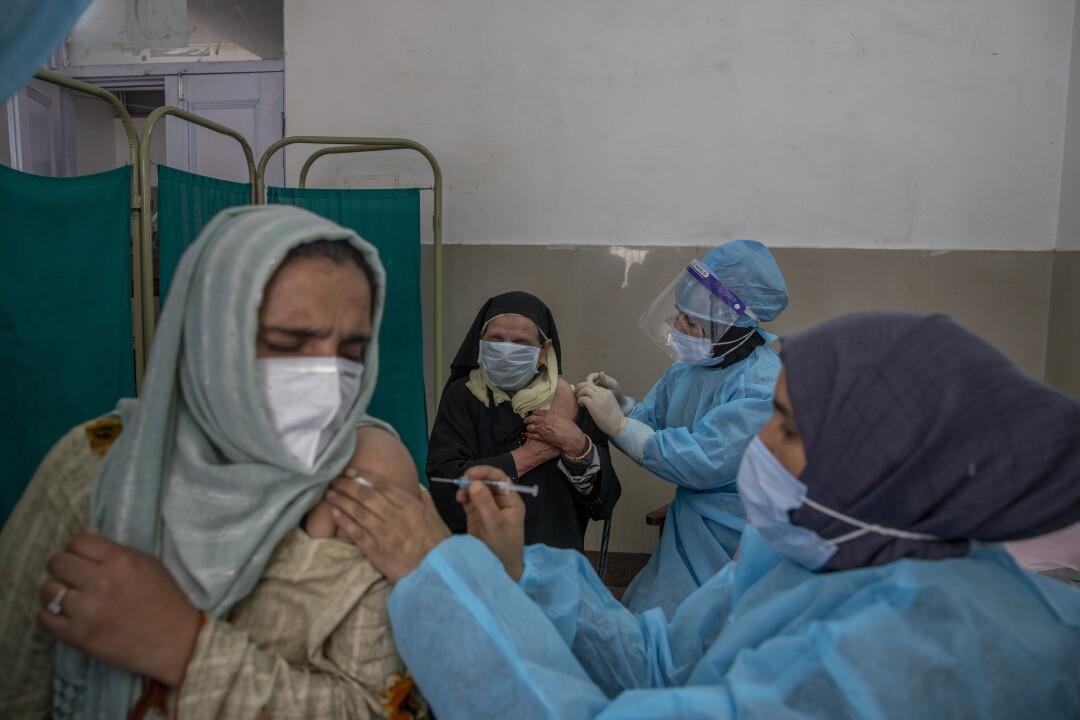 Kashmiri women receive vaccines.
