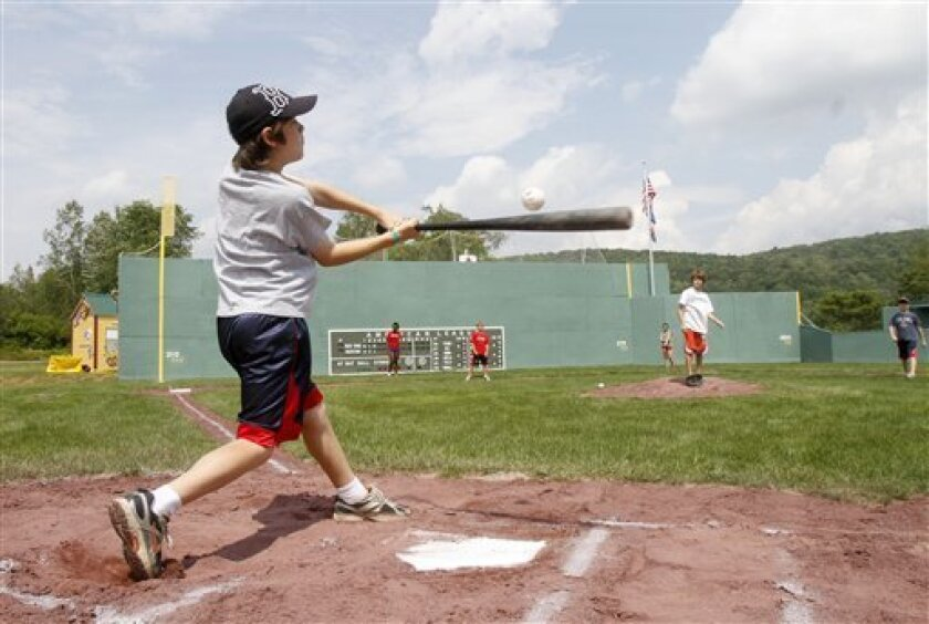 A youngster takes a swing at the plate at Little Fenway, a scaled-down version of the major league field in Essex, Vt., Monday, Aug. 2, 2010. Little Fenway is a unique 1/4th scale replica of Boston's Fenway Park in the backyard of Pat & Beth O'Connor's house in Essex, Vermont. It was built in 2001