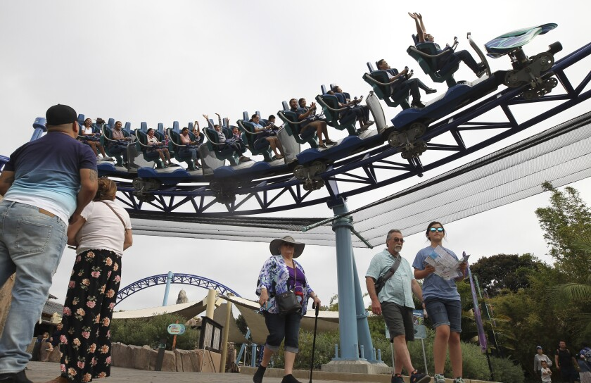 People ride the Manta roller coaster as park visitors walk through SeaWorld on a recent Saturday afternoon.