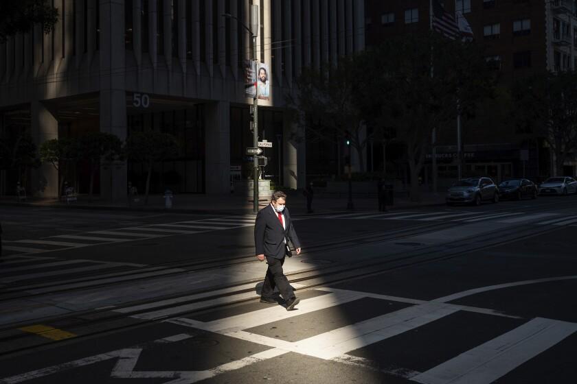 Un trabajador cruza una intersección en el distrito financiero de San Francisco por la tarde