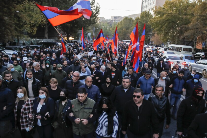 Protesters, a few in masks and some holding Armenian flags, crowd together and lock arms.