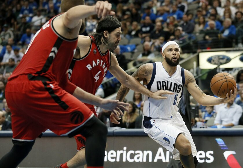 Toronto Raptors' Jonas Valanciunas, left, of Lithuania, and Luis Scola (4), of Argentina, defend on a drive to the basket by Dallas Mavericks' Deron Williams during the second half of an NBA basketball game Tuesday, Nov. 3, 2015, in Dallas. The Raptors won 102-91. (AP Photo/Tony Gutierrez)