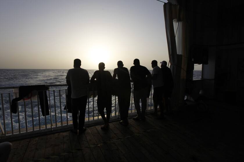 FILE - In this Sept. 22, 2021 file photo, Arab migrants, including three Libyans, two Tunisians and a Moroccan, gaze at the Mediterranean Sea, from the deck of the Geo Barents, a rescue vessel operated by MSF (Doctors Without Borders) in the central Mediterranean Sea, off Libya. Authorities in Libya began a crackdown on migrants Friday, Oct. 1, in the western town of Gargaresh, a major hub for migrants. They rounded up over 5,000 people, and the raids left a migrant shot dead and at least 15 others injured, the U.N. said. Libya has emerged as the dominant transit point for migrants fleeing war and poverty in Africa and the Middle East, hoping for a better life in Europe. (AP Photo/Ahmed Hatem, File)