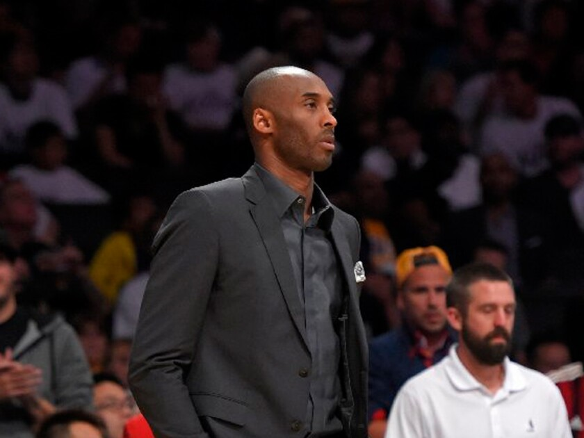 Kobe Bryant stands near the Lakers' bench during a timeout in a game against the Dallas Mavericks on March 8, 2015, at Staples Center.