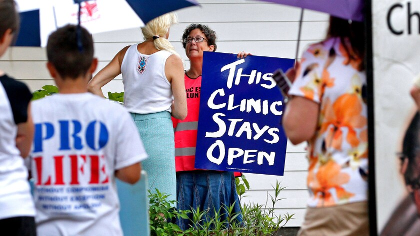 A volunteer at Causeway Medical Clinic in Metairie, La., stands at the entrance July 23 with a sign as antiabortion activists protest outside.