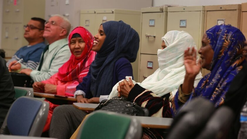 Ayan Sheikh-Mohamed, center, laughs about a question over where to find camel milk in San Diego, as she translates the teacher's words into Arabic in a class at the Alliance for African Assistance in City Heights for new refugees.