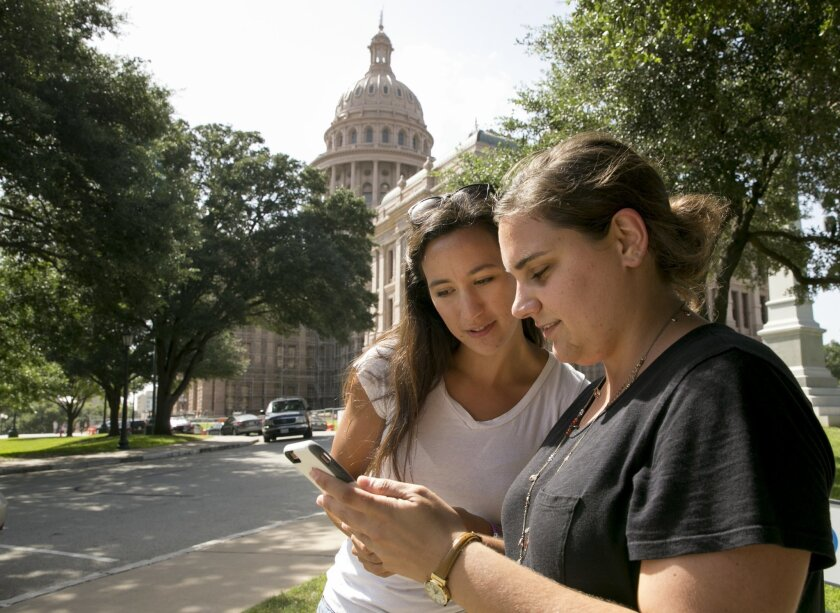 Tina Bizaca, left, and Sarah Boutwell play the augmented-reality smartphone game Pokémon Go at the Capitol in Austin, Texas, Monday July 11, 2016. (Jay Janner/Austin American-Statesman via AP)