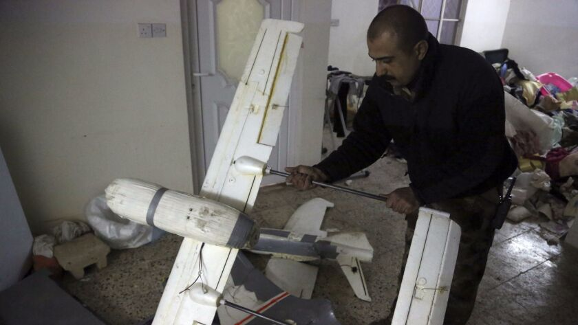 An Iraqi officer in Mosul inspects a drone that belonged to Islamic State militants