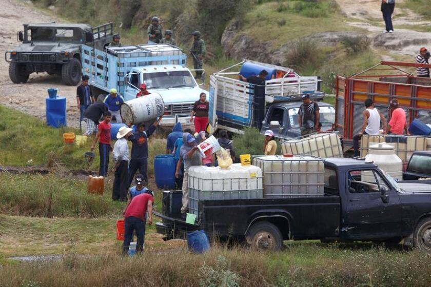 Fotografía del 23 de octubre de 2017 de pobladores que llenan grandes bidones de combustible de una toma clandestina ante la mirada de elementos del Ejercito Mexicano en la localidad de San Francisco Tlaloc, en el estado de Puebla (México). EFE/Archivo
