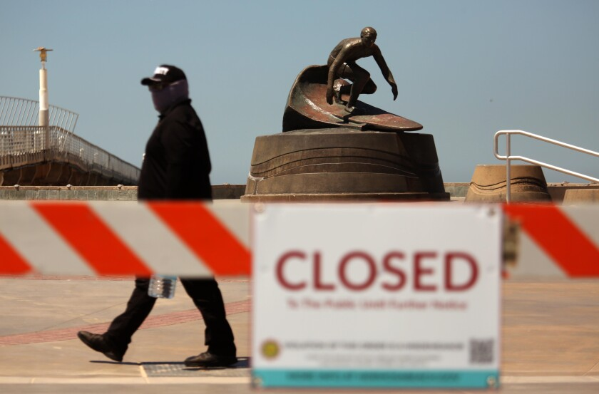 A security guard walks by a statue of surfer Dewey Weber April 23 as he patrols the Strand in Hermosa Beach.