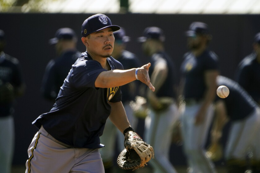 FILE - Milwaukee Brewers' Keston Hiura tosses the ball during the team's spring training baseball workout in Phoenix , in this Tuesday, Feb. 23, 2021, file photo. Hiura had been Milwaukee's starting second baseman for the last two years but is moving over to first as the Brewers make room for newly acquired Kolten Wong at second.(AP Photo/Jae C. Hong, File)