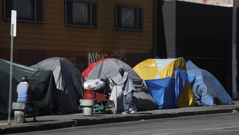 A homeless man pushes his shopping cart to outside his tent located on 7th Street near Stanford Avenue in downtown Los Angeles. An outbreak of typhus has been linked to overcrowding and homelessness in the area.