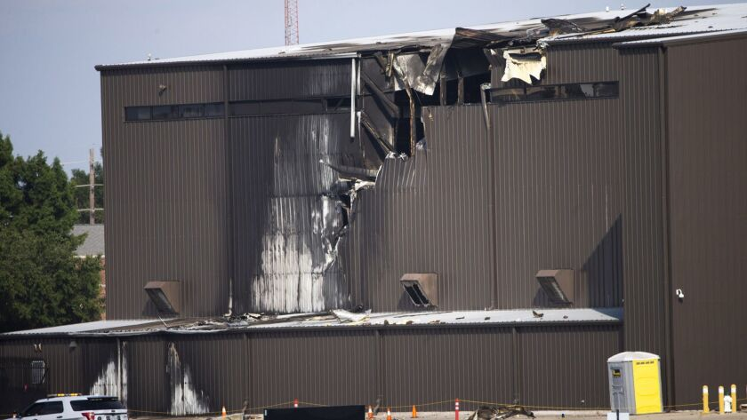Damage is seen to a hangar after a twin-engine plane crashed into the building at Addison Airport in
