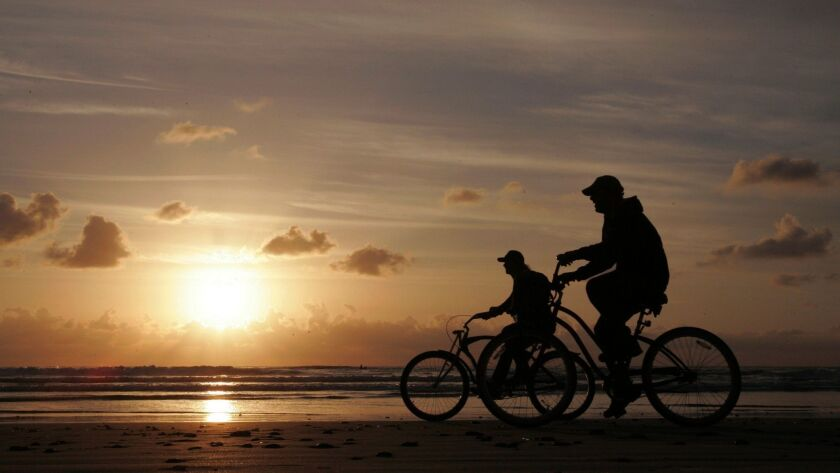 Two bicyclists ride along the water's edge at sunset at Cardiff State Beach along South Coast Highway in Encinitas.