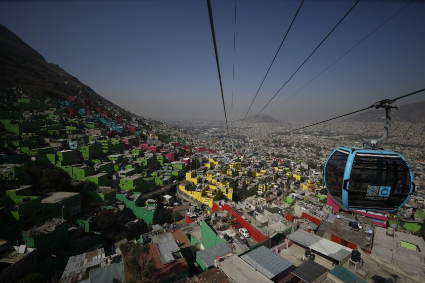 Aerial view of blue sky tram hanging from cables stretched over a dense, colorful neighborhood