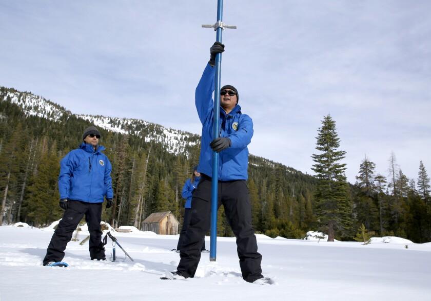 Sean de Guzman, chief of snow surveys for the California Department of Water Resources, measures the snowpack during the first survey of the season at Phillips Station near Echo Summit, west of Lake Tahoe.
