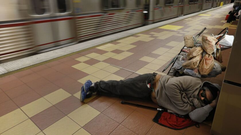 LOS ANGELES, CA JANUARY 31, 2018: As the Red line leaves a person sleeps next to their cane insi