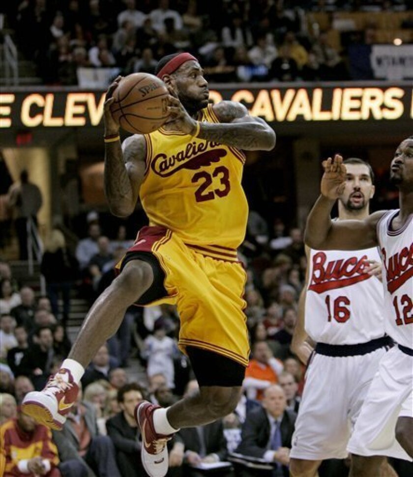 Cleveland Cavaliers' LeBron James (23) passes the ball in front of New Orleans Hornets' Peja Stojakovic (16), of Serbia,  and Hilton Armstrong  in the first quarter in an NBA basketball game, Friday, Jan. 16, 2009, in Cleveland. (AP Photo/Tony Dejak)