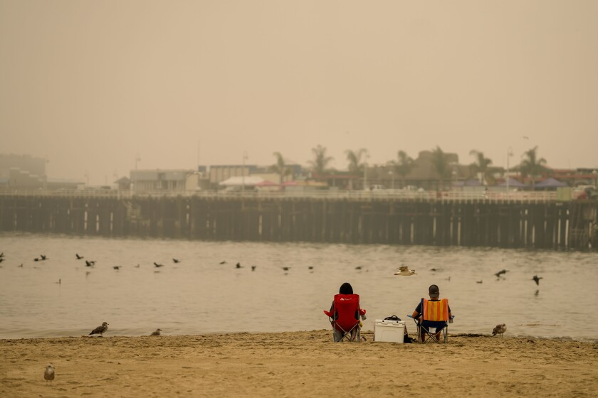 People sit on an empty beach in Santa Cruz as smoke from the wildfires obscures the view of the Santa Cruz Wharf.