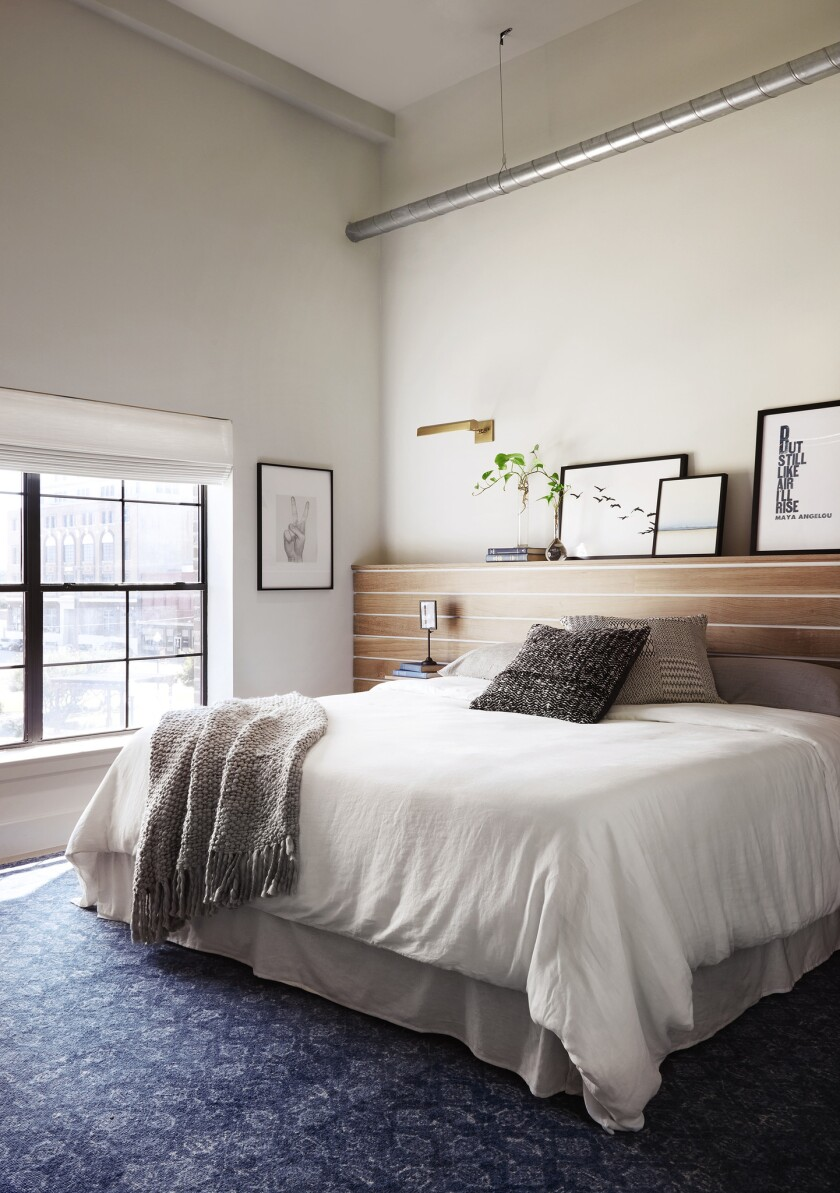 A wood-paneled half-wall creates a built-in headboard and doubles as a shelf for books, art and plan