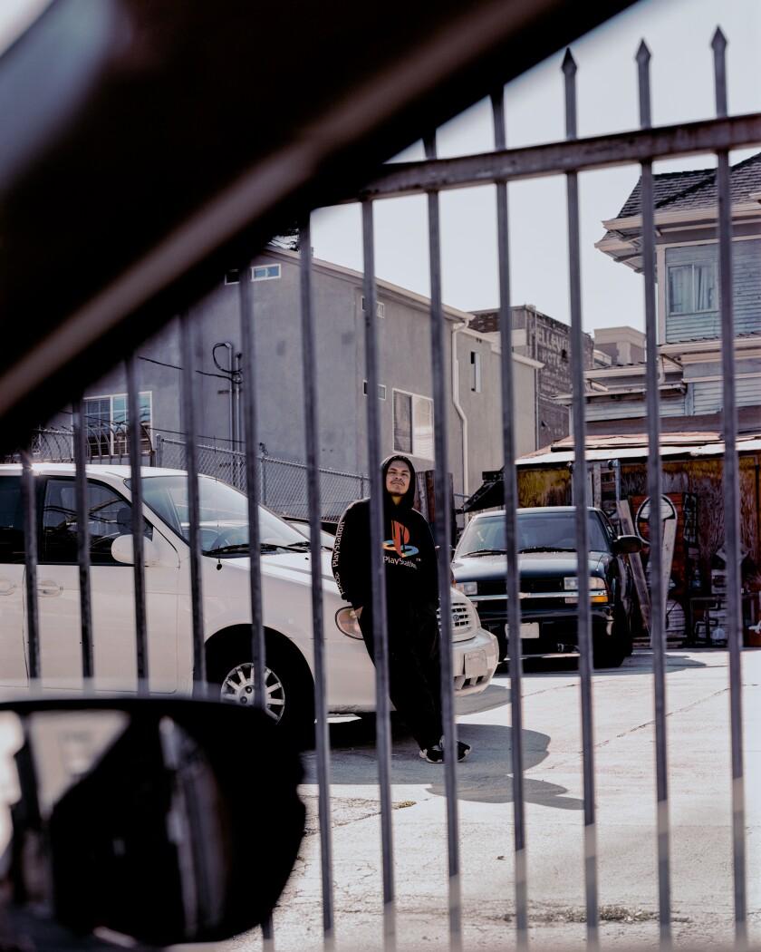 Josh Vasquez se para detrás de una cerca en el estacionamiento de su casa.