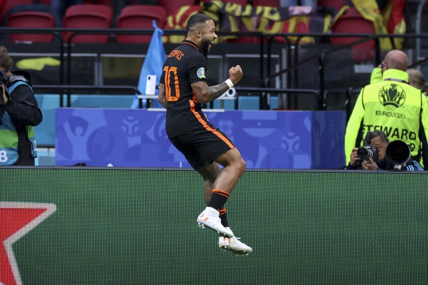 Memphis Depay of the Netherlands celebrates after scoring his side's opening goal during the Euro 2020 soccer championship group F match between North Macedonia and Netherlands, at the Johan Cruyff ArenA in Amsterdam, Netherlands, Monday, June 21 2021. (Kenzo Tribouillard/Pool via AP)