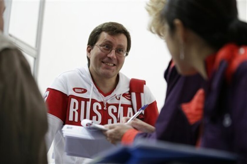 Russia's Alexei Klimov talks with Olympic news service reporters after qualifying for the final in the men's 25-meter rapid fire pistol event, at the 2012 Summer Olympics, Friday, Aug. 3, 2012, in London. (AP Photo/Rebecca Blackwell)