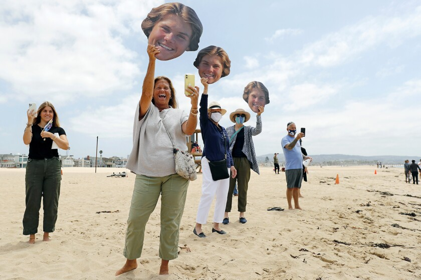 Christy Brigandi cheers and waves a photo of her son Johnny, a Newport Harbor senior, as he joins a graduation walk.