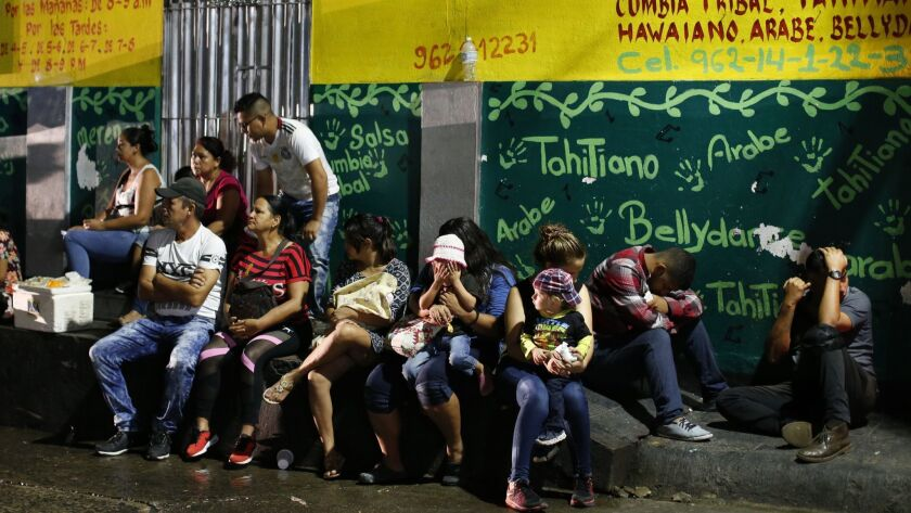 Migrants wait before dawn outside the offices of the Mexican Commission for Refugee Assistance, wher
