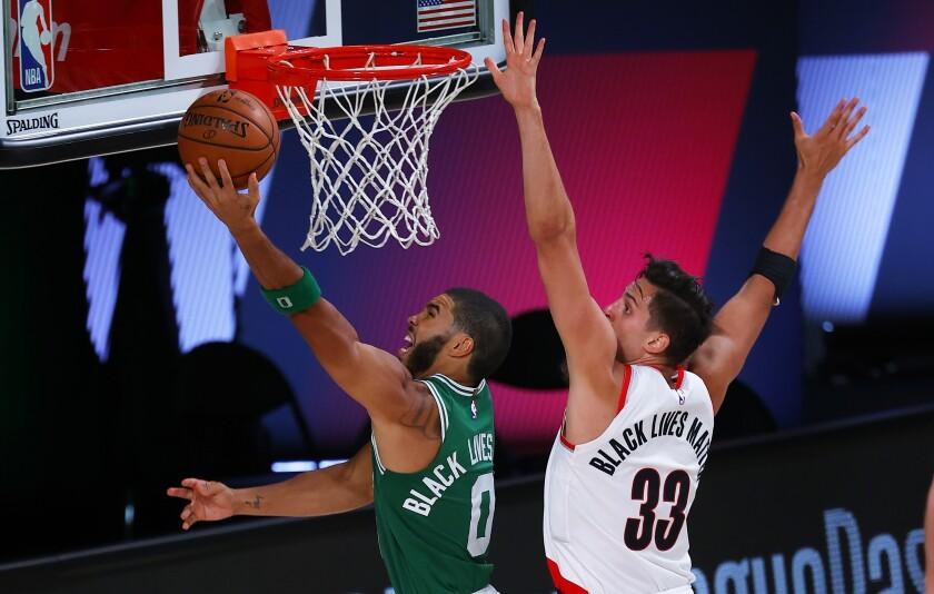 Jayson Tatum (0), encesta por los Celtics de Boston ante Zach Collins, de los Trail Blazers de Portland, en juego del domingo 2 de agosto de 2020, en Lake Buena Vista, Florida. (Mike Ehrmann/Pool Photo vía AP)