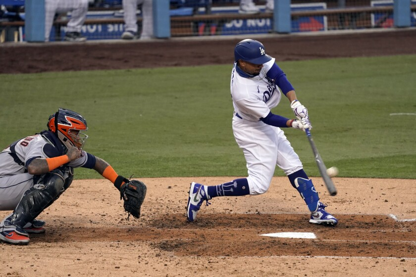 Dodgers right fielder Mookie Betts hits a two-run home run in front of Houston Astros catcher Martin Maldonado.